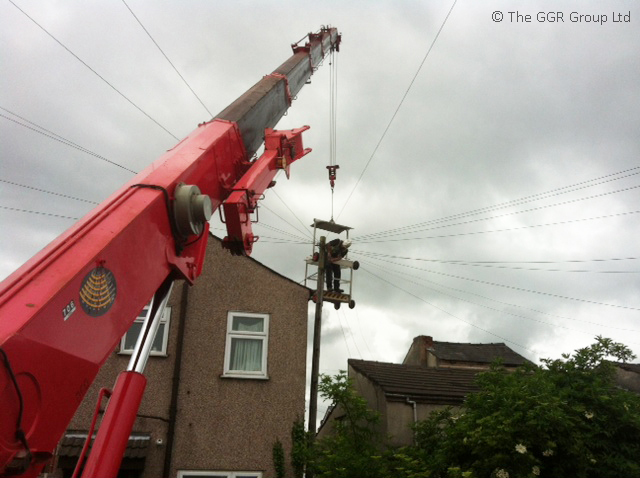 Telecoms repair working using mini crane and man basket