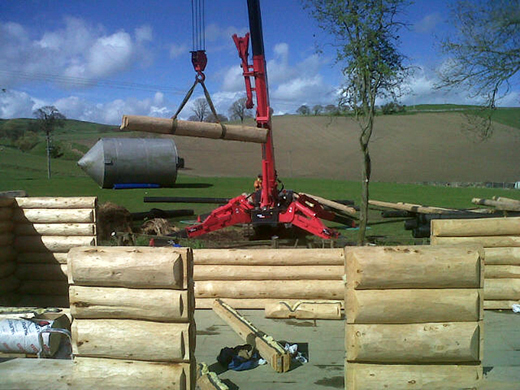 UNIC URW-706 lifting logs for cabin construction