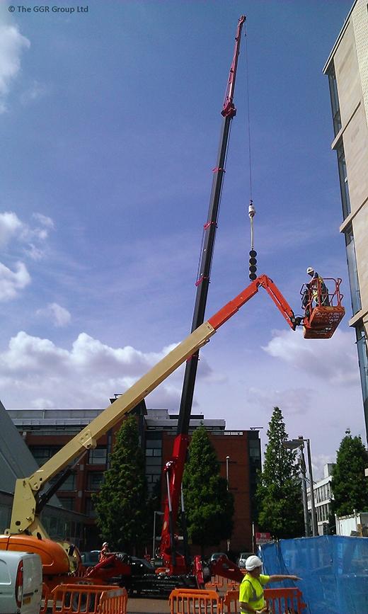 UNIC URW-1006 mini crane installing glazing at Manchester apartment block