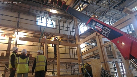 UNIC URW-376 lifting wooden beams at indoor theatre