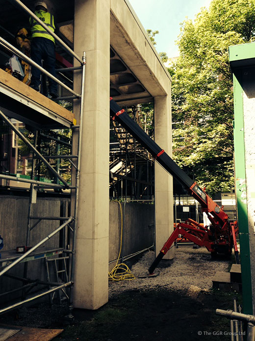 UNIC mini spider crane working in a restricted access area