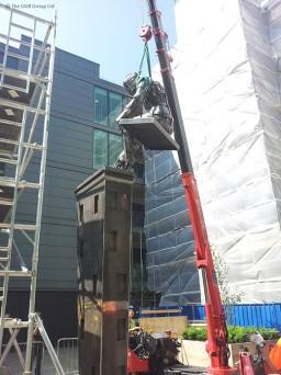UNIC URW-376 crane lifts figure on top of statue